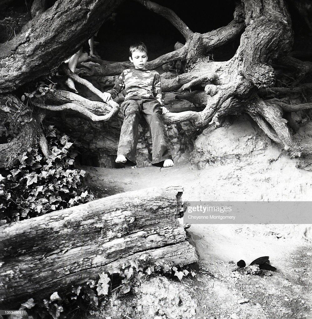 Boy sitting on roots : Stock Photo