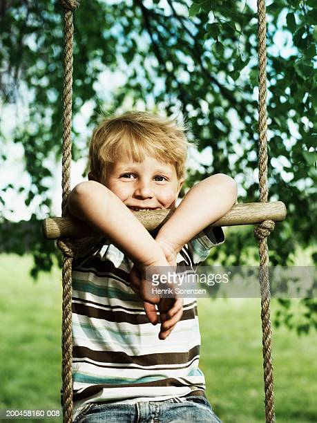 Boy (3-5) sitting on rope ladder hanging from tree, smiling, portrait
