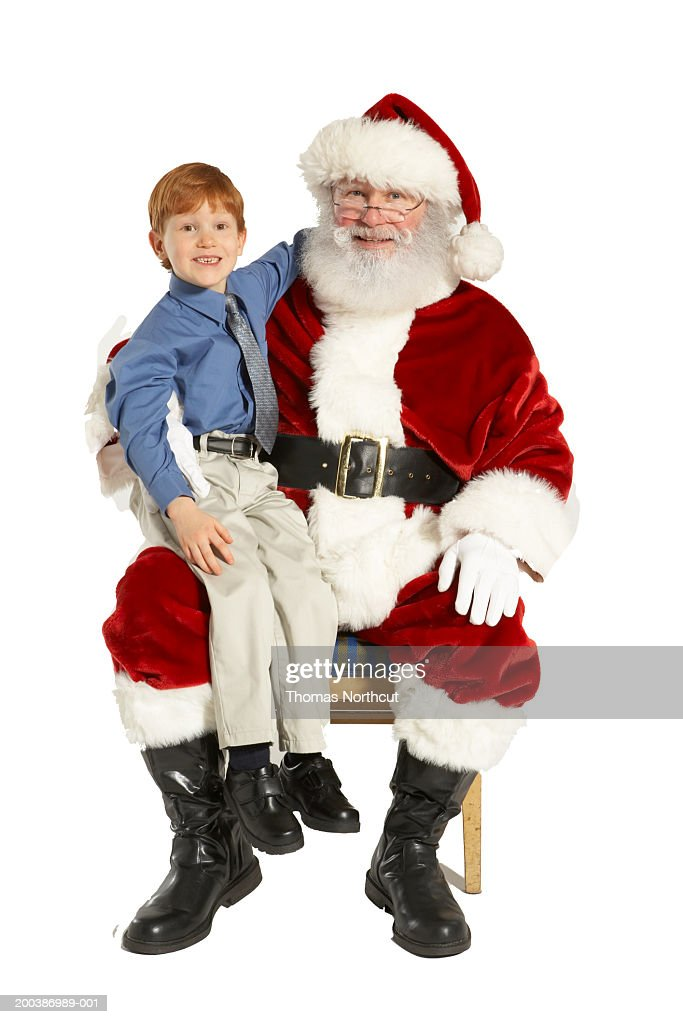 Boy (4-6) sitting on Santa's lap, smiling, portrait