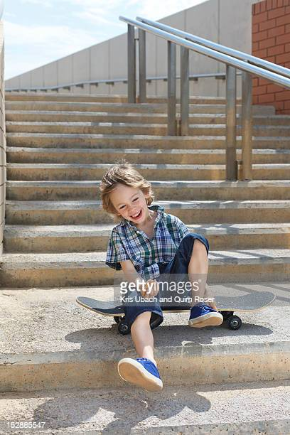 Boy sitting on skateboard on steps