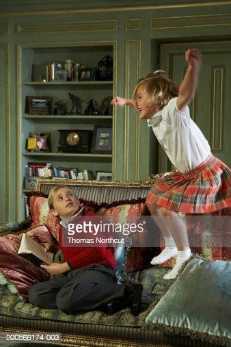 Boy (8-10) sitting on sofa holding book, sister (5-7) jumping on sofa : Stock Photo