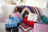 Boy (6-7) sitting on sofa, reading birthday card, elevated view