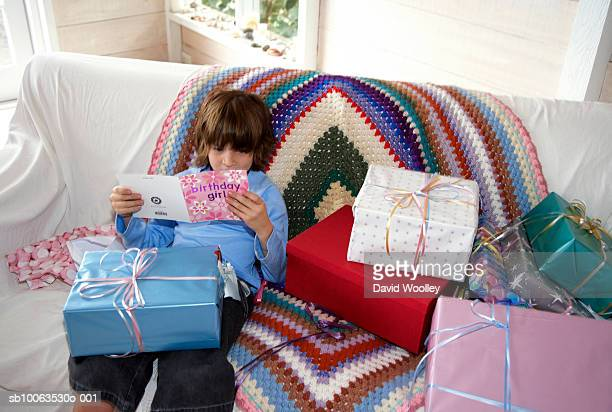 Boy (6-7) sitting on sofa, reading birthday card, elevated view