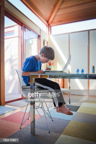 boy,7, sitting on stack of books using a laptop : Stock Photo