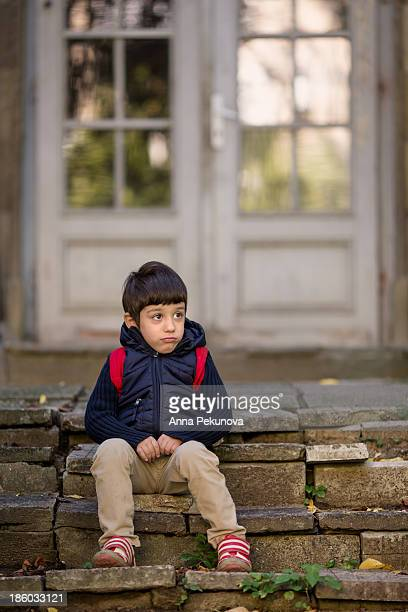 Boy sitting on stone stairs looking away