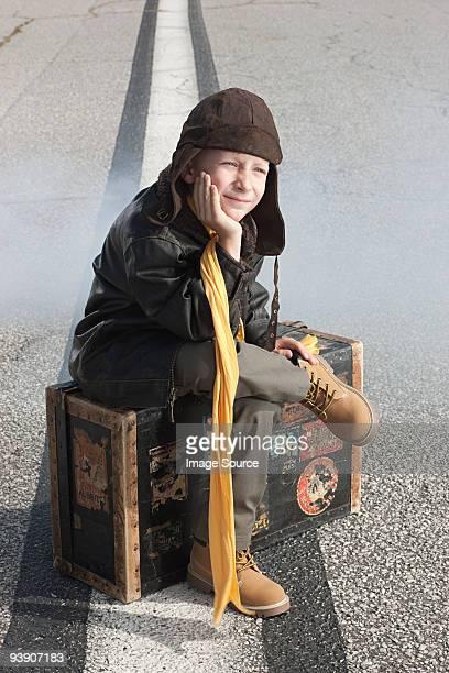 Boy sitting on suitcase on runway