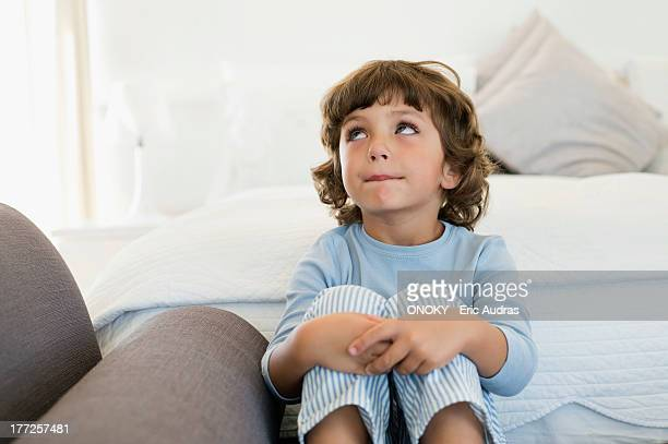 Boy sitting on the bed looking up