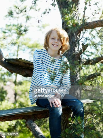Boy sitting on tree house : Stock Photo