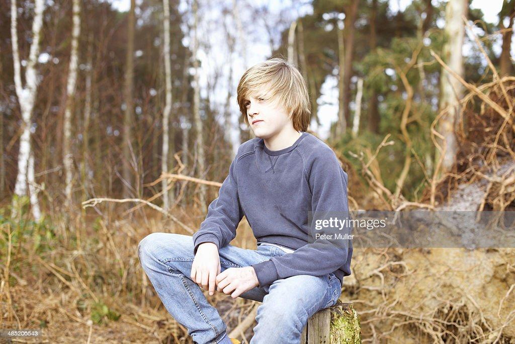 Boy sitting on tree stump in forest
