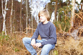 Boy sitting on tree stump in forest