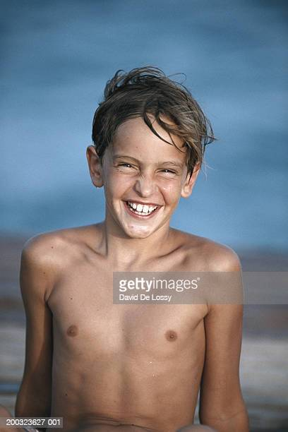 Boy (8-11) sitting outdoors, smiling, portrait