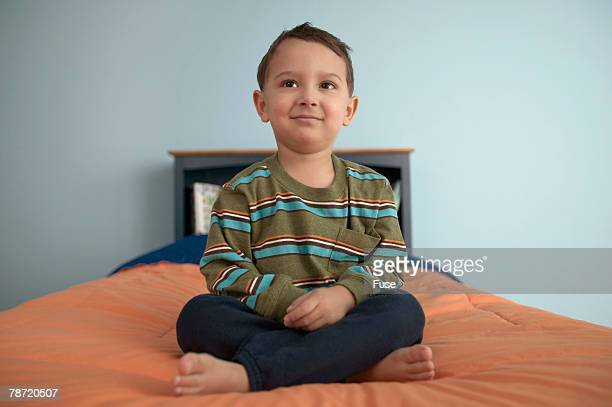 Boy Sitting Quietly on Bed