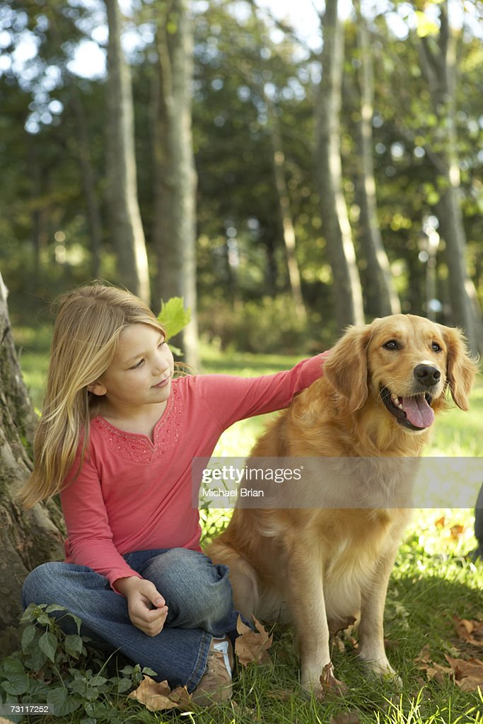 Boy (4-5) sitting with dog on lawn in park : Stock Photo