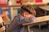 Boy sitting with head down on classroom desk