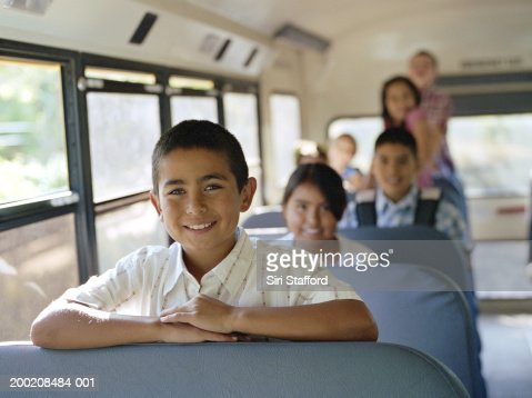 Boy (9-11) sitting with other students on school bus, portrait : Stock Photo