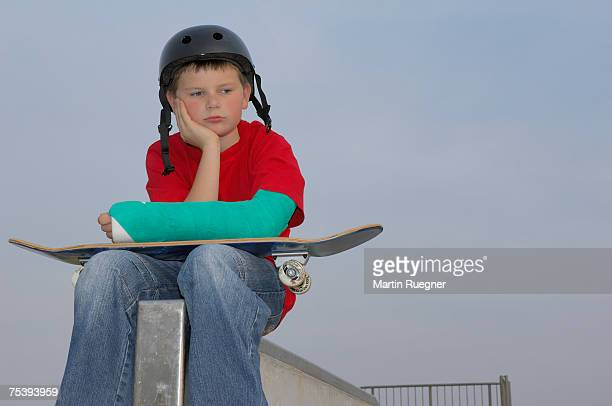 Boy (8-9) sitting with skateboard, arm in plaster