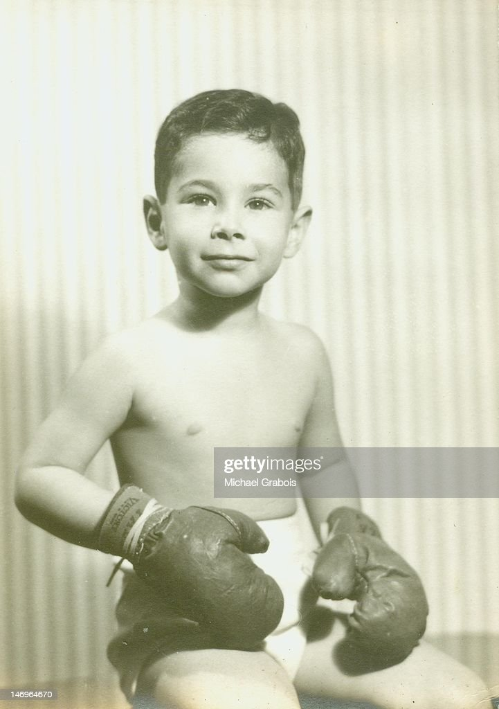 Boy sitting with wearing boxing gloves : Stock Photo