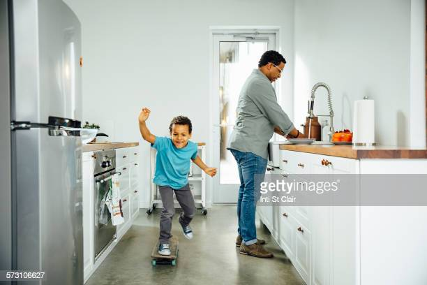 Boy skateboarding near father in kitchen