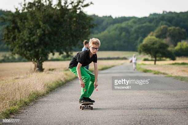 Boy skateboarding on a rural street