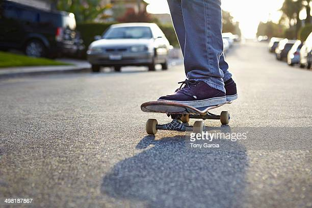 Boy skateboarding on road, close up