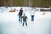 Happy boy skating with his parents on background