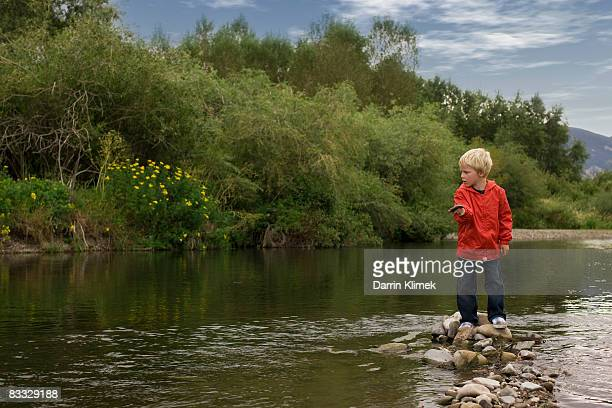 Boy skipping rocks in river