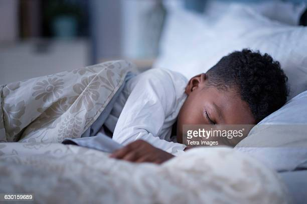 Boy (6-7) sleeping in bed