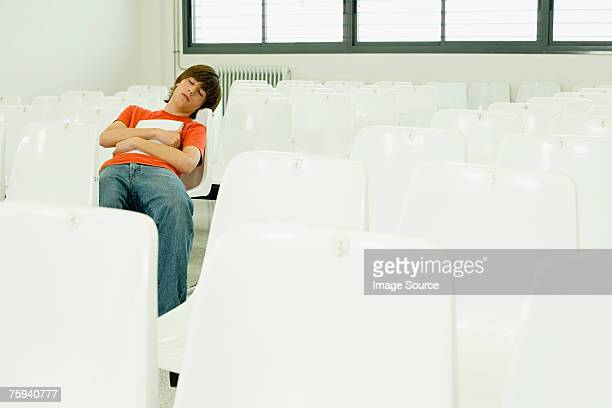 Boy sleeping in lecture theatre