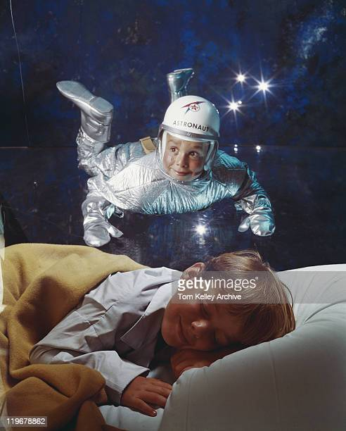 Boy sleeping on bed dreaming of astronaut