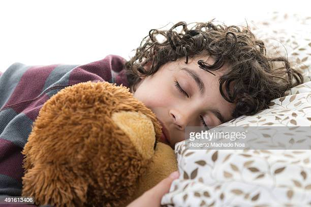 Boy sleeping on bed holding a soft toy by his side against white background The photo represents innocence of children