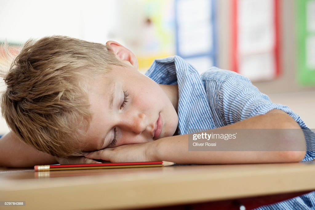 Boy sleeping on desk in classroom : Stock Photo