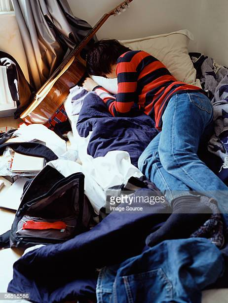Boy sleeping on messy bed