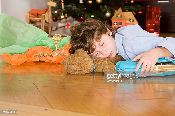 'Boy sleeping under Christmas tree, holding toy car'