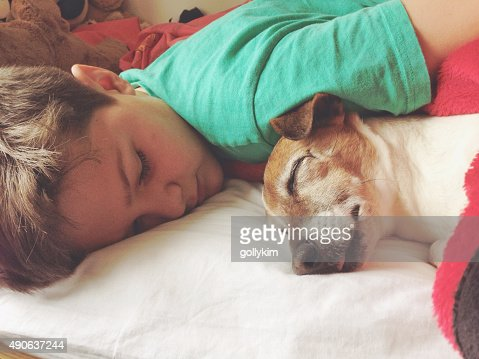 Boy sleeping with dog : Stock Photo