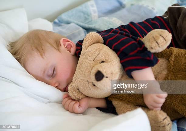 Boy sleeping with his teddy bear