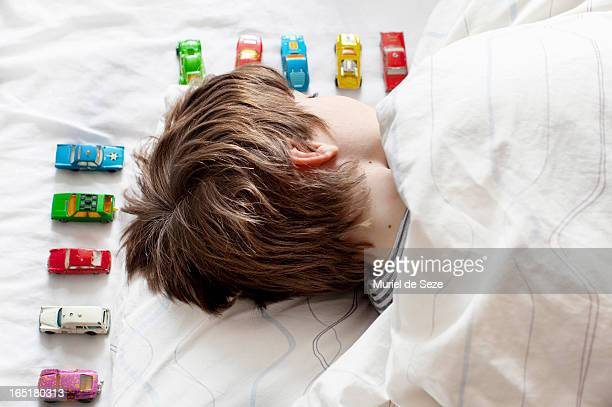 Boy sleeping with toy cars