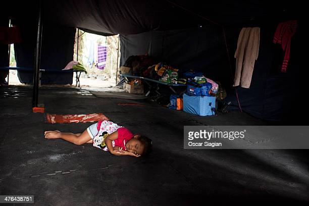 A boy sleeps inside makeshift shelter at a makeshift shelter for hundreds of people that displaced because forrest fires after his home was destroyed...