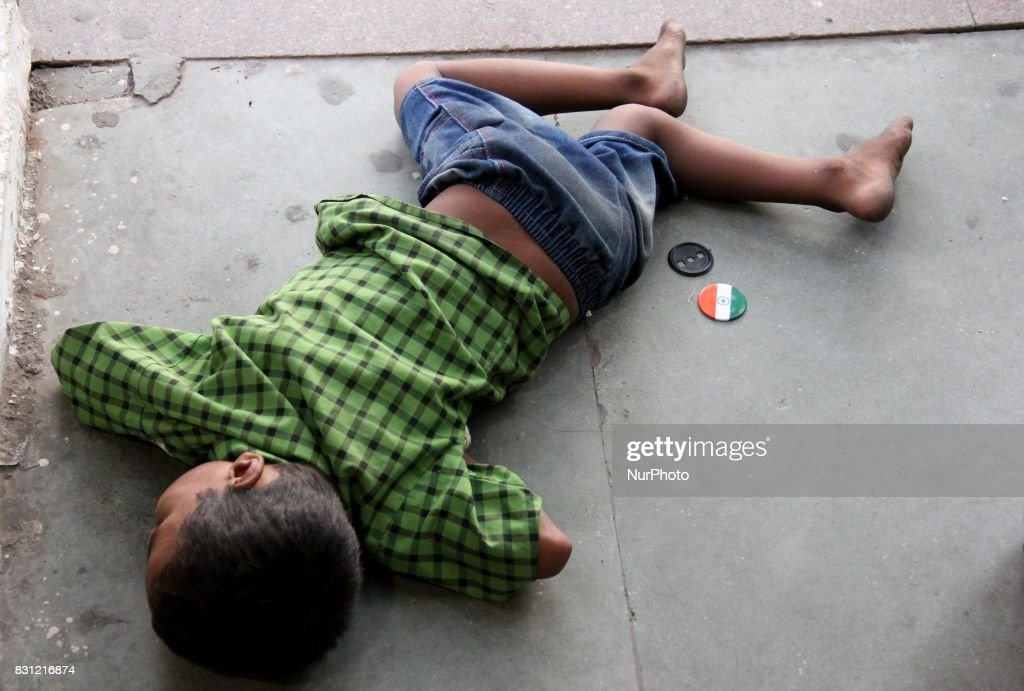 A Boy sleeps on the road side ahead of the Independence Day at Cannaught Place in New Delhi, India, on 14 August 2017.