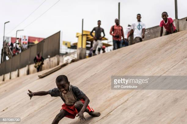 A boy slides down from the containment walls of a train track of the Viana district in Luanda on August 22 2017 With current president Dos Santos...