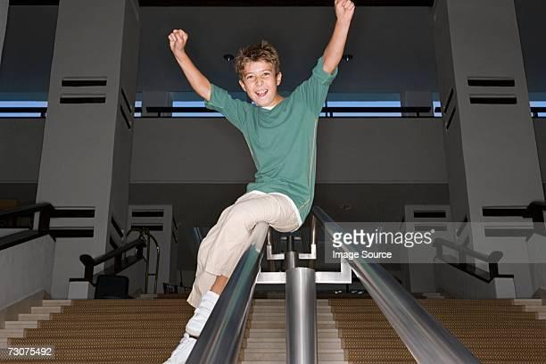 Boy sliding down a banister