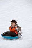 Boy sliding down a hill on a toboggan