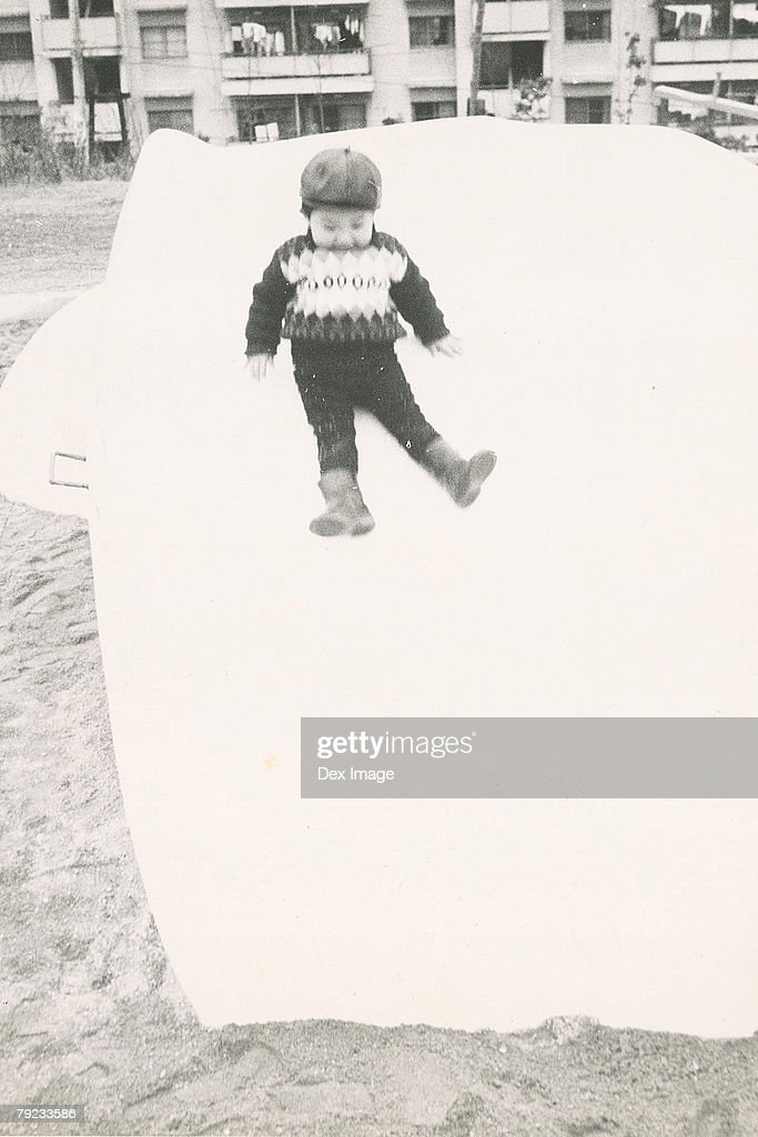 Boy sliding down a slide : Stock Photo