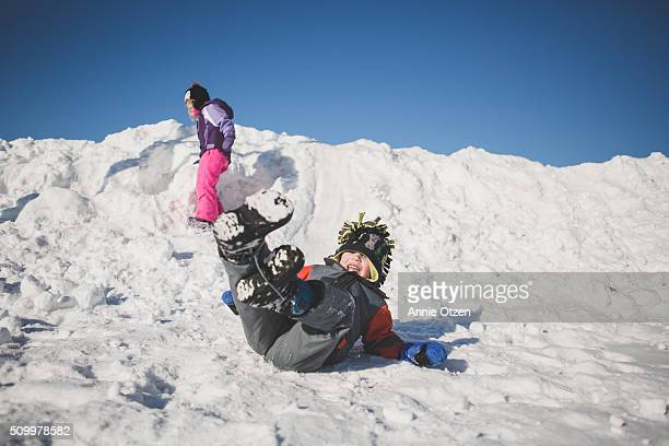 Boy Sliding Down Snow Pile