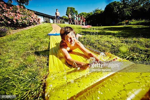 Boy sliding down water slide in backyard