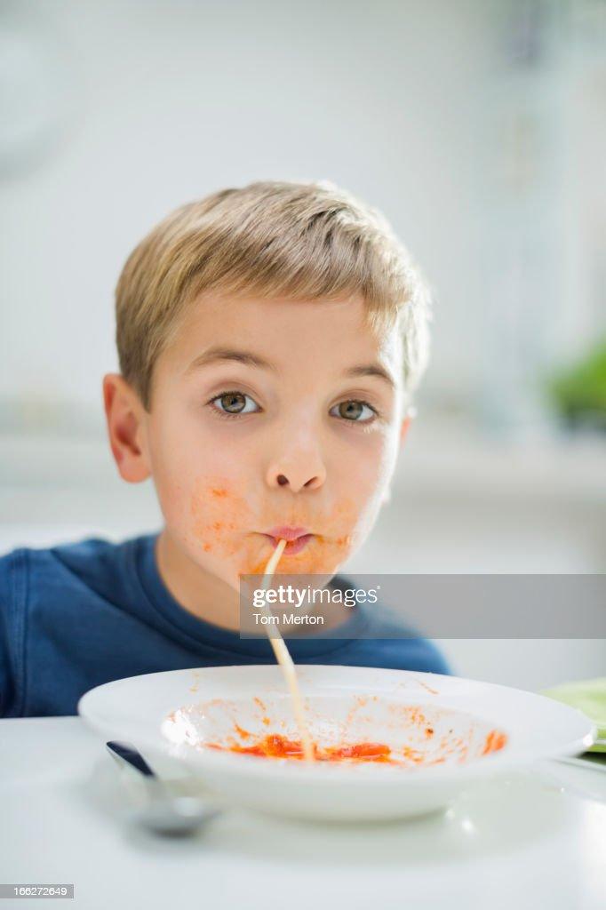 Boy slurping spaghetti at table : Stock Photo