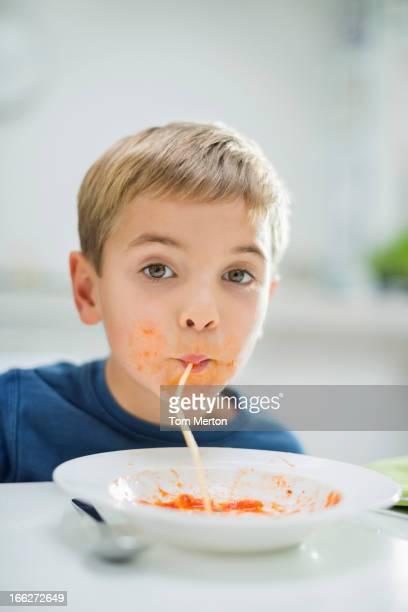 Garçon slurping spaghetti à table