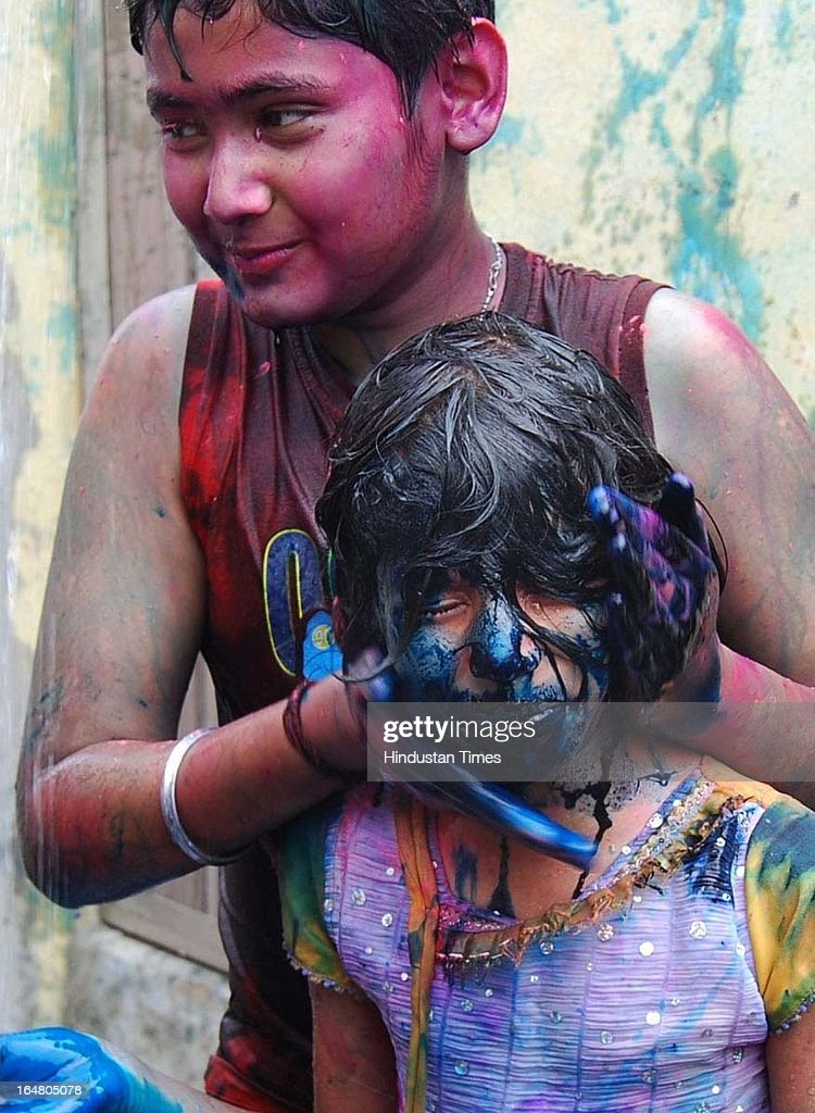 A boy smearing face of girl with colors during Holi festival celebration on March 28, 2013 in Allahabad, India. Holi, festival of color is Hindu religious festival also called Basantotsav or spring festival as it mark the arrival of spring. People gather together to play colors, sing and dance to traditional tunes and eat sweets specially Gujiyas.