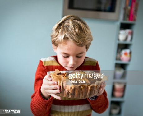 Boy smelling an apple cake he has made : Stock Photo