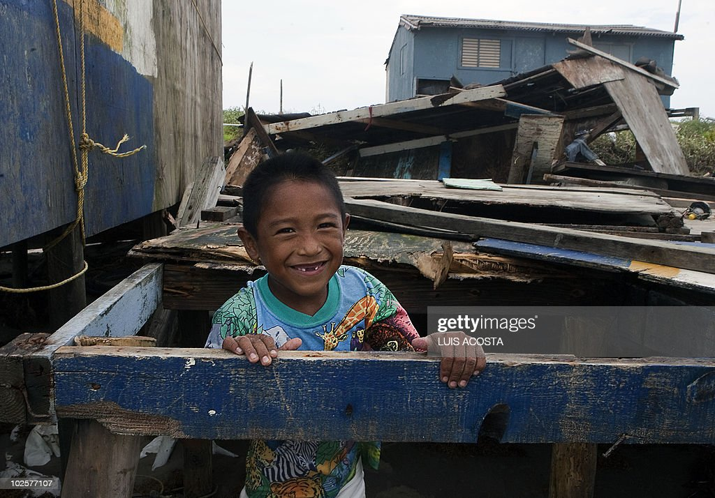 A boy smiles at the photographer amidst the remains of a damaged house after the passage of Hurricane Alex, in Matamoros, Tamaulipas State, on July 1, 2010. Alex, the first hurricane of the Atlantic season, weakened across northeast Mexico as it neared high mountains on Thursday, after disrupting oil clean-up operations in the Gulf of Mexico. Alex was downgraded to a tropical storm after roaring ashore late Wednesday as a Category Two hurricane slightly south of the eastern US-Mexico border. AFP PHOTO/Luis Acosta