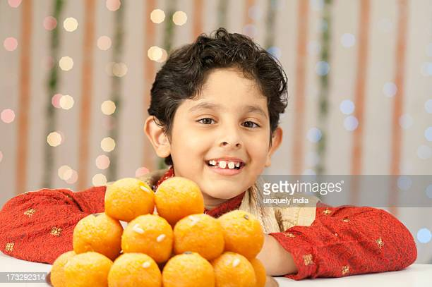 Boy smiling and a stack of laddoo on Diwali
